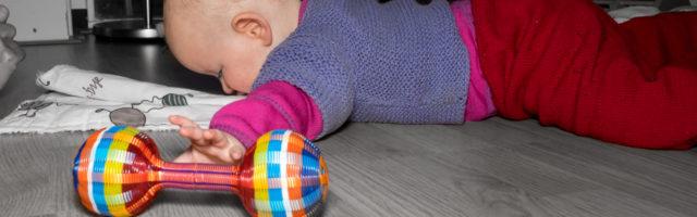 Baby reikt naar speeltje