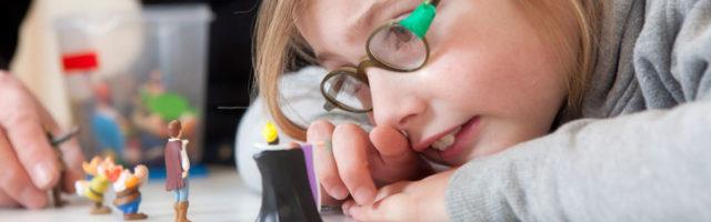 basisschoolleerlinge kijkt naar miniatuurpoppetjes