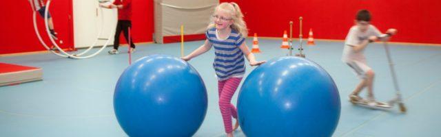 sport meisje rolt 2 grote blauwe ballen